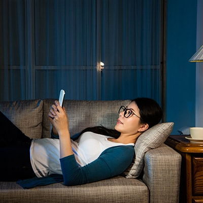 a lady using mobile phone on sofa at night for the 24-hour online FX services