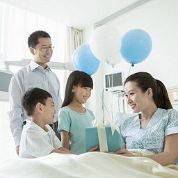 a family in hospital ward, kids are giving a gift and balloon to lady