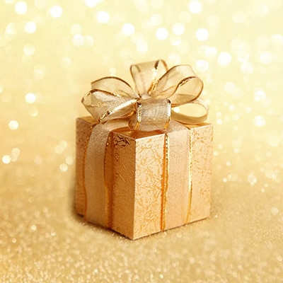 a golden gift box with shiny gold ribbons