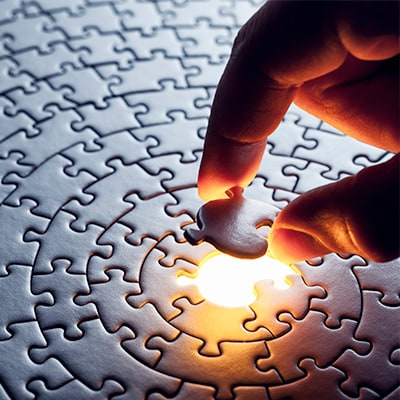 A hand placing a last peice of puzzle