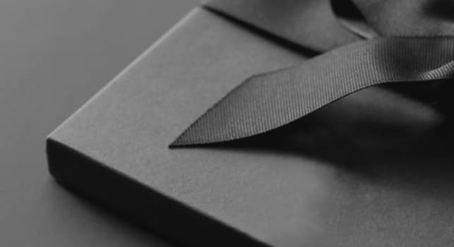 Grey scale image of a gift wrapped with ribbon