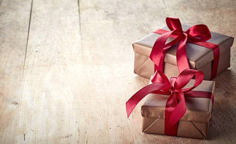 2 gift wrapped by brown papers and red ribbon on the wooden floor
