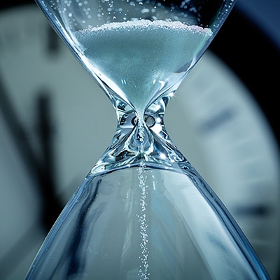 an hourglass with a clock background