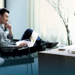 Young chinese man working with laptop in office