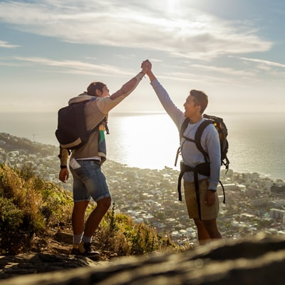 gentlemen high-five for successfully climbing up to a mountain