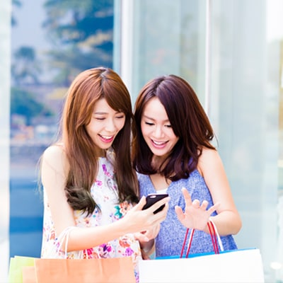 2 ladies with shopping bags are using mobile phone