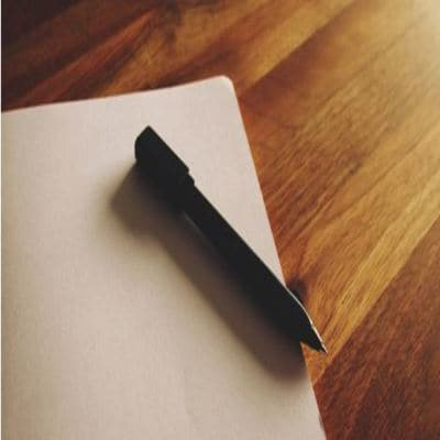 a notebook with a pen on the wooden floor