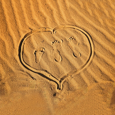a heart shape with 2 adults and 1 kid's footprint on the sand