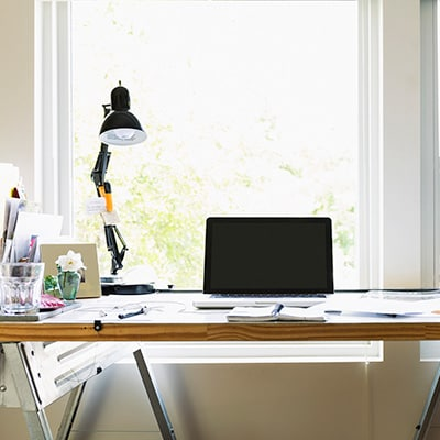 a working desk with lamps, laptop, notebook, and blueprints, by the window.