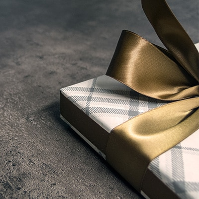 A gift box with a golden ribbon and checker wrap