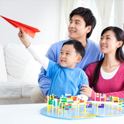 一對爸媽正與他們的孩子玩紙飛機