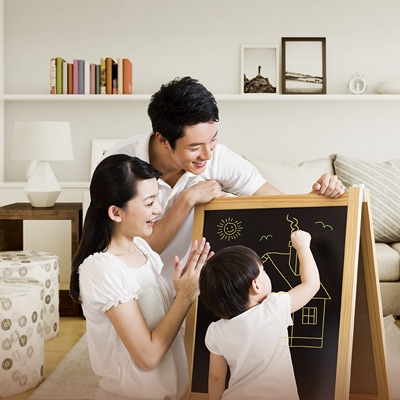 爸媽鼓勵著他們的孩子在黑板上畫出房屋
