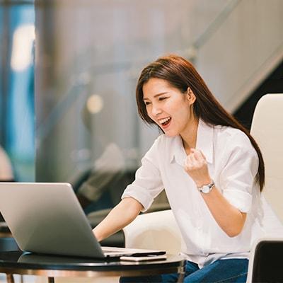一位女士在手提電腦前表現得興奮
