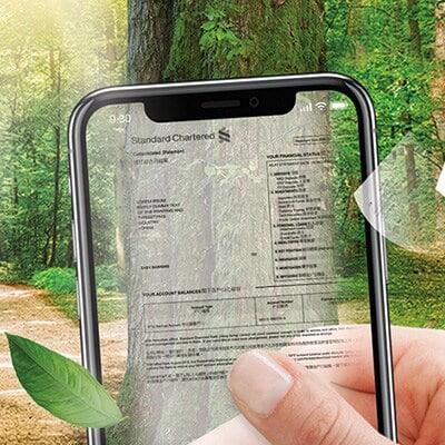 一隻手拿著顯示電子月結單的透明手機,背景透現出綠色樹林