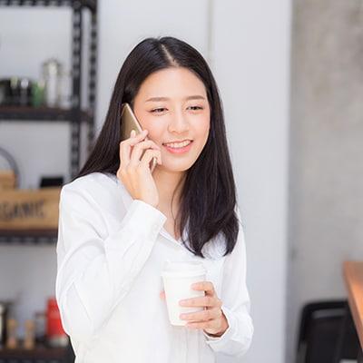 一位女士手持飲料並以手提電話通話