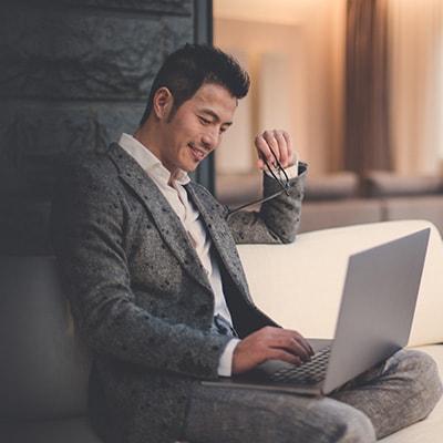 一名男性手持眼鏡並使用電腦
