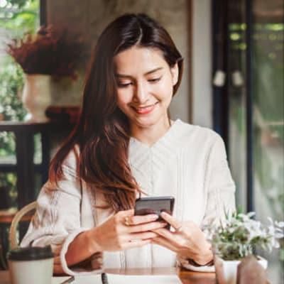 """"""" 長頭髮的女士在咖啡館裡微笑著使用手機"""""""