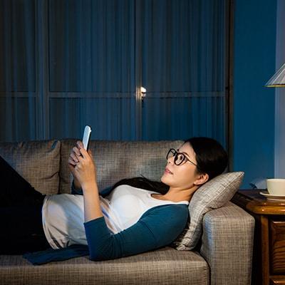 一位女士在沙發上使用手提電話