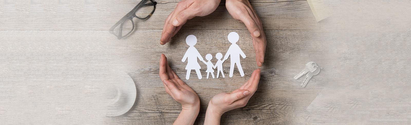 兩雙手在桌上護著一個象徵家庭的剪紙