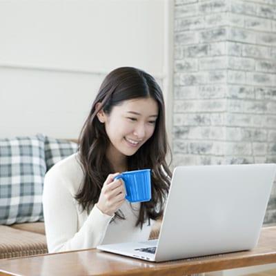 一位女士在享用飲料和使用手提電腦