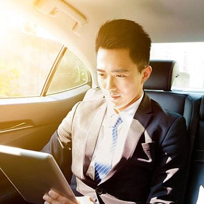 一位身穿西裝的男性在車上使用平板電腦