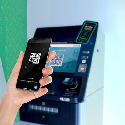一隻手拿著手機在 ATM 機前,兩個屏幕都顯示一個二維碼QR code