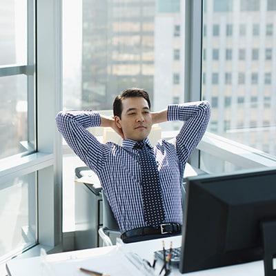 一個男生悠哉地在私人辦公室看著電腦螢幕