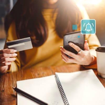 女人拿著信用卡,她的手機彈出短信或電子郵件通知