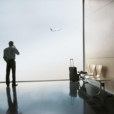 一位男士在窗前看著飛機起飛
