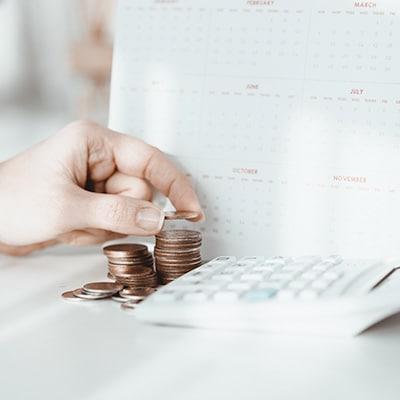 在計算機前堆疊硬幣,旁邊放著月曆