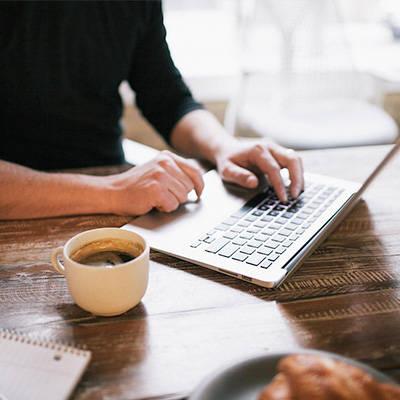 一名男性正在使用手提電腦,旁邊放著咖啡