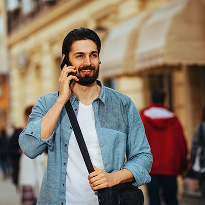 Handsome businessman talking on the phone on the street