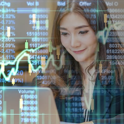Business financial concept double exposure of happy asian businesswoman sitting on working space and looking the stock market exchange information and trading graph in the modern office
