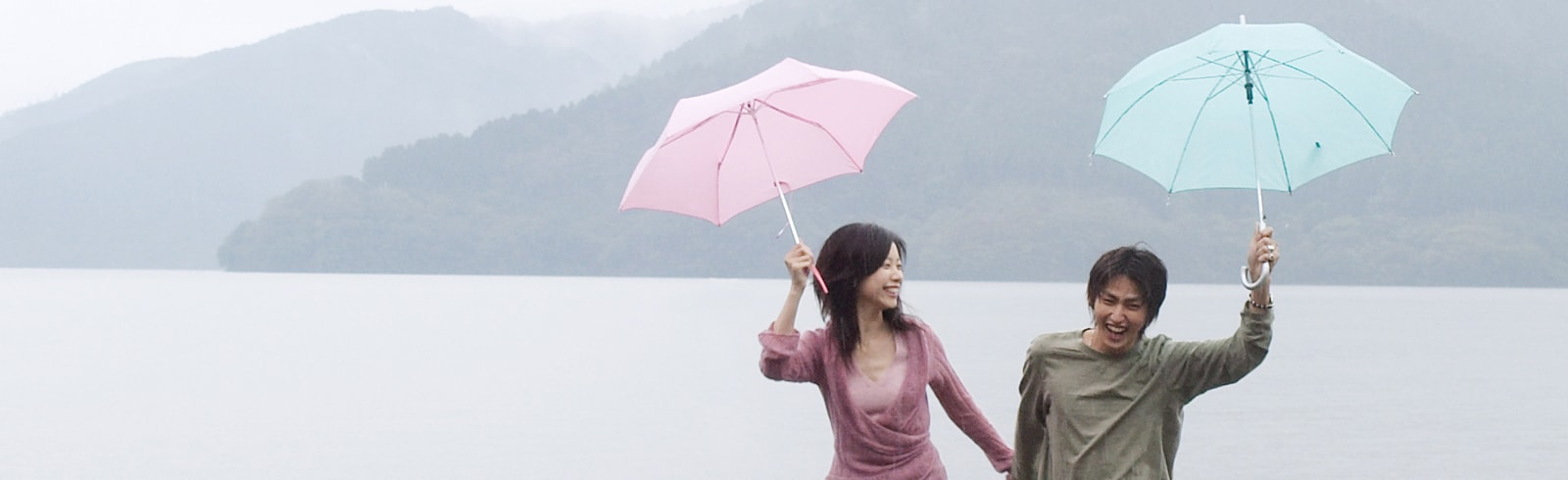 Couple holding an umbrella in the rain laughing