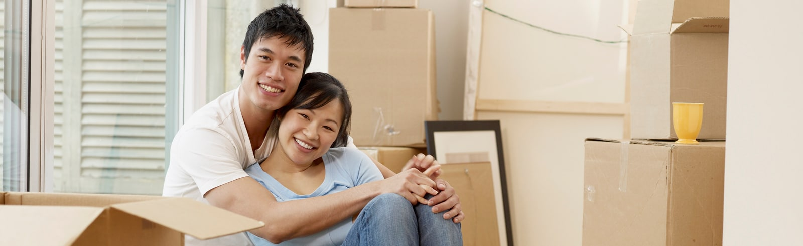 Asian couple sitting amid packing boxes
