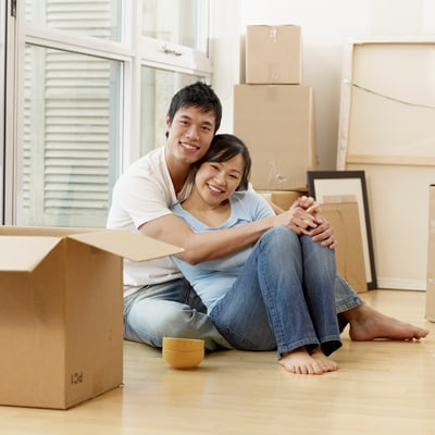 Asian couple surrounded by moving boxes