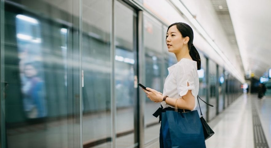 Young woman carrying shopping bag using smartphone while waiting for subway in platform