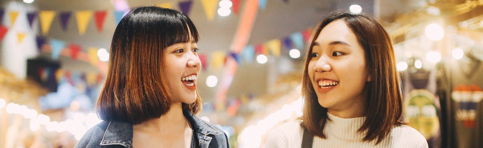 Two happy singaporean girls chatting on a main stree