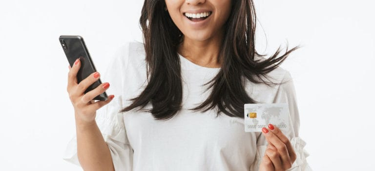 Joyous asian woman wearing casual clothing looking at camera with surprise while holding credit card and smartphone in hands isolated over white background