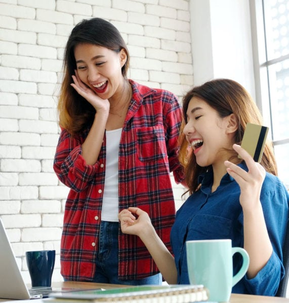 Happy asian women spend money by credit card for shopping online two asian friends use electronic money to pay online shopping sale with happiness e commerce asia woman and online banking payment