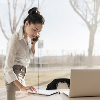 Asian businesswoman on the phone and using digital tablet