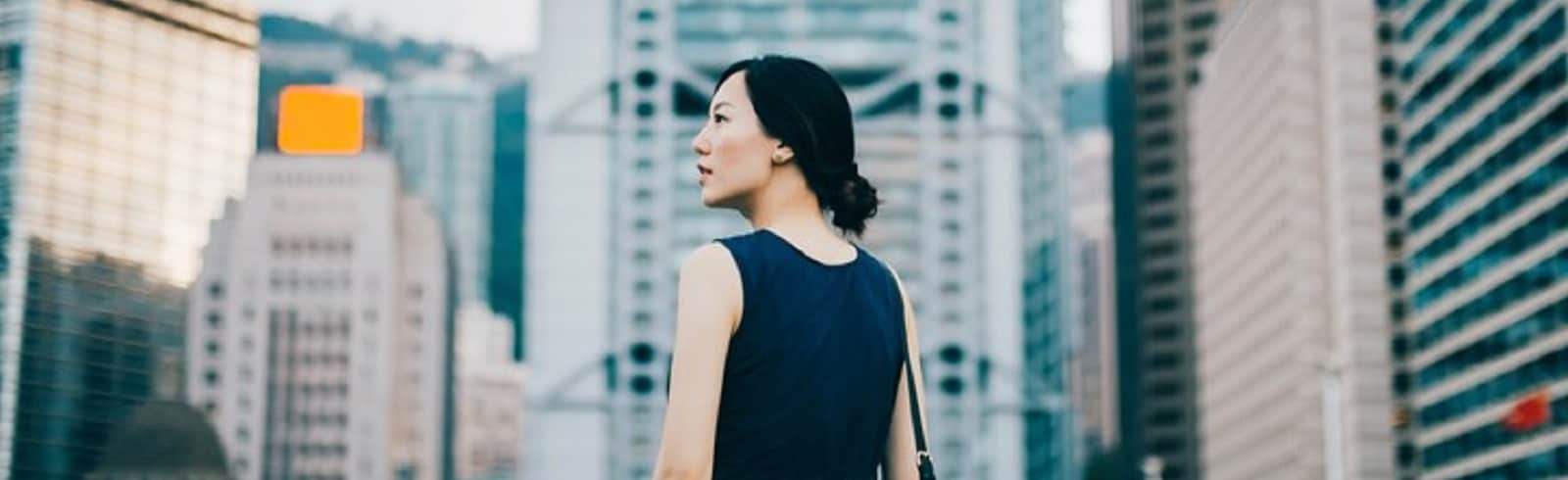 Successful young businesswoman looking away with confidence standing against urban cityscape